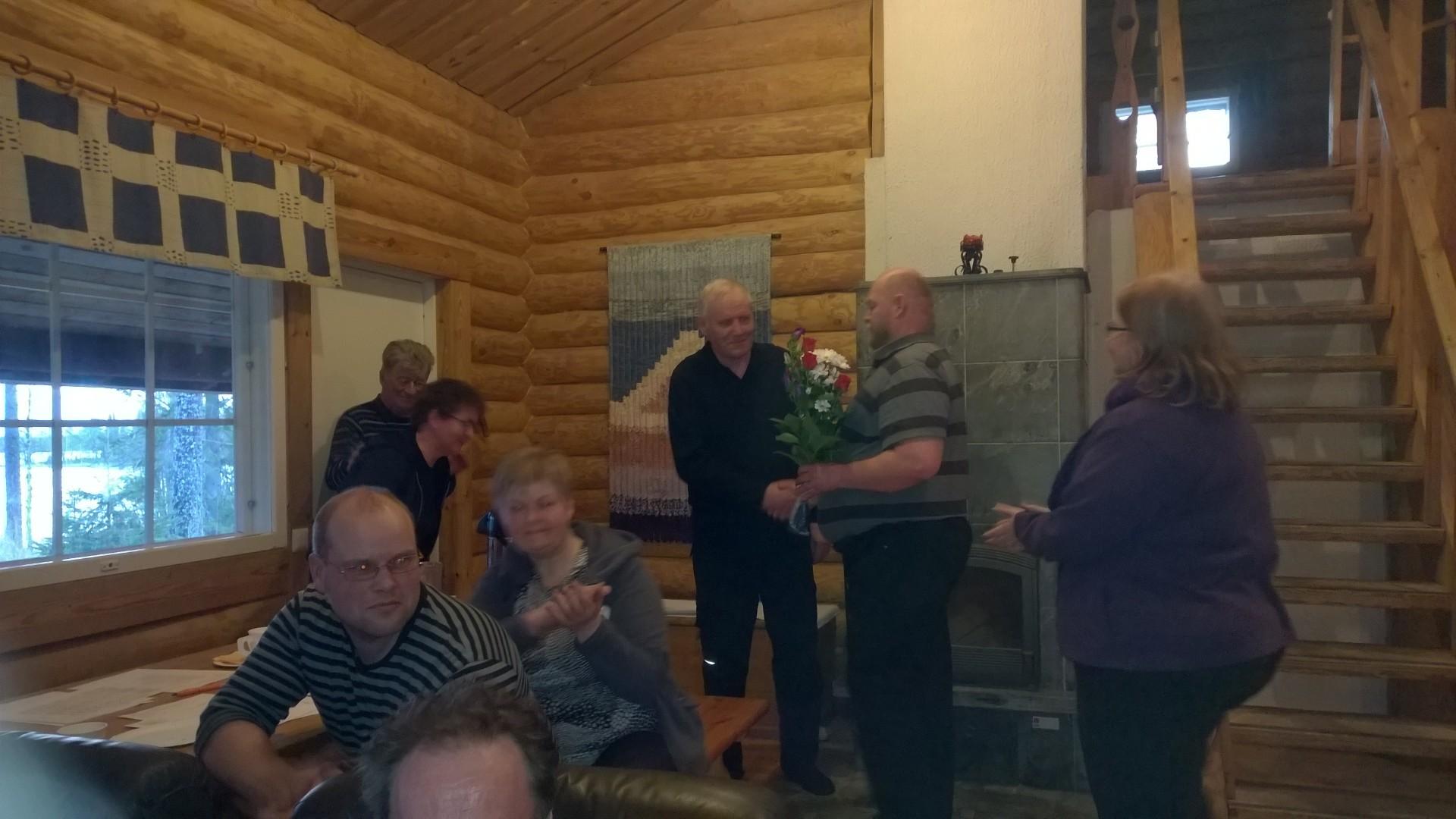 Kyläpäällikkö Juhani Tiainen ojentaa kukat yhdistyksen ensimmäisille kunniajäsenille, Marja ja Antti Väistölle.